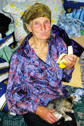 Photo of Zavastita Andrei with kitten and banana in her home in Popricani, Iasi, Romania, taken in August 2012